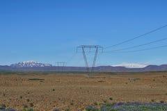 Corrente elettrica principale dei piloni alti di elettricità alta con alte montagne e cielo blu nei precedenti in Islanda Immagini Stock Libere da Diritti