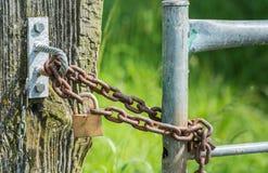 Corrente oxidada e um cadeado endurecido fechado do fim fotos de stock royalty free