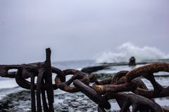 Corrente oxidada no cais do mar escuro imagens de stock