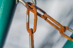 A corrente oxidada pendura em uma cerca azul na tarde imagens de stock