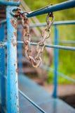 A corrente oxidada pendura em uma cerca azul na tarde imagem de stock