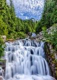Corrente precipitante a cascata nel parco nazionale di Mt. Ranier con il cielo Fotografia Stock