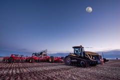 Corrente rapida, SK/Canada- 10 maggio 2019: Luna piena sopra il trattore a cingoli ed il martello pneumatico di Bourgault nel cam fotografia stock libera da diritti