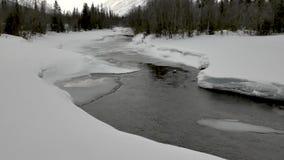 Correnti del fiume da sotto la copertura di neve nell'ombra della montagna stock footage