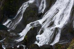 Correnti separate di un funzionamento sulle rocce nere, Islanda della cascata Fotografia Stock Libera da Diritti