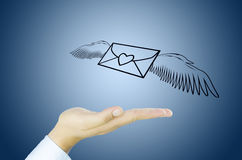Correo con el ala del ángel en la mano humana Foto de archivo libre de regalías