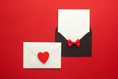 Correo, corazón y cinta del sobre en fondo rojo Concepto del saludo de Valentine Day Card, del amor o de la boda Visión superior Fotos de archivo libres de regalías