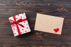 Correo del sobre con la caja roja del corazón y de regalo sobre fondo de madera oscuro Concepto del saludo de Valentine Day Card, imagen de archivo libre de regalías