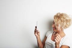 Correo electrónico de fabricación femenino elegante de Selfie o de Cheking vía Smartphone mientras que se opone al fondo blanco y Foto de archivo