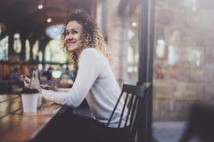 Correo electrónico hermoso encantador de la lectura de la mujer joven en el teléfono móvil durante tiempo de resto en cafetería B imagen de archivo libre de regalías