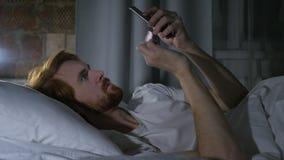 Correo electrónico y mensajes de la ojeada del hombre de la barba del pelirrojo en el teléfono en cama almacen de video