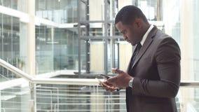 Correos electrónicos afroamericanos de la lectura del hombre de negocios en su smartphone y respuestas que mandan un SMS Foto de archivo