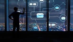 Correos electrónicos con el hombre por las ventanas grandes en la noche imagenes de archivo