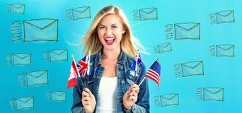 Correos electrónicos con la mujer joven con las banderas Imagenes de archivo