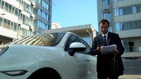 Correos electrónicos en el teléfono cerca del coche, aplicaciones de la lectura del empresario de negocio la compañía imagen de archivo