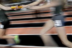 Correr una carrera de retransmisión en zona que da del bastón Fotos de archivo
