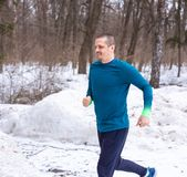 Correre adulto dell'uomo del corridore all'aperto nell'inverno fotografia stock libera da diritti