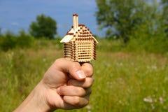 Corresponda con la pequeña casa que se coloca en un puño femenino Imágenes de archivo libres de regalías