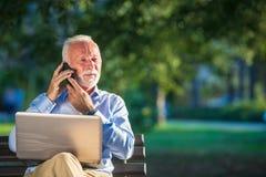 Correspondance d'affaires Homme d'affaires mûr focalisé utilisant l'ordinateur portable tout en se reposant en parc photographie stock libre de droits