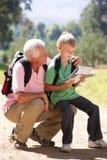 Correspondencia de la lectura del hombre mayor con el nieto fotografía de archivo libre de regalías