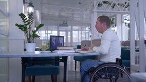 Correspondencia que estudia, hombre del alumno inválido en la silla de ruedas que hace notas en el cuaderno que se sienta en la t metrajes