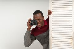 Correspondent black handsome man taking pictures of a spicy scene, he makes intriguing news, which is not yet known to anyone. Correspondent black handsome man Royalty Free Stock Image