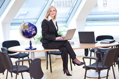 Corresponding good looking businesswoman. Is sitting on her desk with the laptop in her hands stock photo