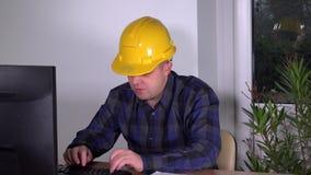 Corretor de imóveis bem sucedido novo do supervisor da construção no escritório que faz o trabalho no computador filme