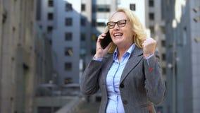 Corretor de imóveis fêmea envelhecido que mostra sim o gesto que fala no telefone, aprovação do negócio de negócio video estoque