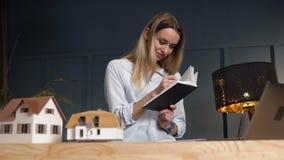 Corretor de imóveis fêmea pensativo com o caderno nas mãos durante o trabalho no escritório video estoque