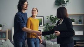 Corretor de imóveis de sorriso que dá a chave aos novos proprietários e a agitar as mãos, beijo dos pares filme
