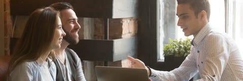 Corretor de seguro que diz ao casal novo sobre a oferta da hipoteca fotos de stock royalty free
