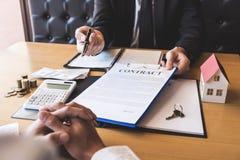Corretor do agente imobiliário que dá a pena aos bens imobiliários de assinatura do contrato do acordo do cliente com formulário  imagens de stock
