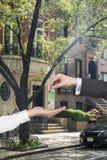 Corretor que entrega uma chave Imagem de Stock Royalty Free
