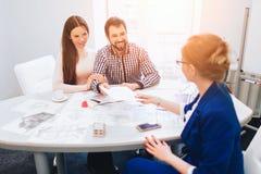 Corretor seguro With Home Sellers atrás Os pares novos da família compram bens imobiliários da propriedade do aluguel Doação do a imagens de stock royalty free