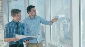 Corretores de imóveis que discutem o projeto de construção em um escritório moderno video estoque