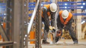 Correzione dei lavoratori del movimento lento con gli scaffali del metallo dei trapani in magazzino video d archivio