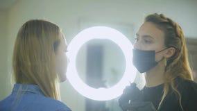 Correzione del sopracciglio Il cosmetologo mette la pittura sulle sopracciglia del ` s del cliente con la spazzola video d archivio