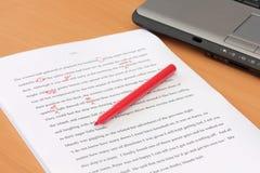 Correzione delle bozze del manoscritto al lato del computer portatile Fotografia Stock