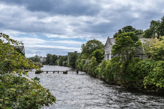 Corrib River rushes through Galway, Ireland. Galway, Ireland - August 3, 2017: The Corrib River rushes between green trees and gray houses to the ocean under Stock Photography