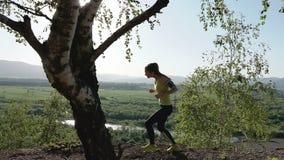 Corrida - corredor da menina que movimenta-se no trajeto de floresta nas montanhas Fuga fêmea caucasiano apta do atleta do modelo video estoque