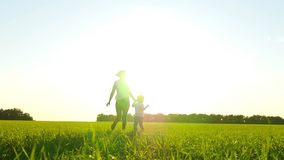Corrida da mãe e da criança ao longo da grama verde através do campo no por do sol em um movimento lento filme