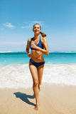 Corrida da praia Mulher da aptidão no biquini que corre no verão Imagens de Stock