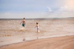 A corrida das crianças ao longo da praia e salpica com a água Fotografia de Stock