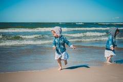 Corrida de duas meninas longe das ondas Imagens de Stock Royalty Free