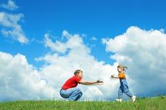 Corrida de la niña al abrazo de la madre en hierba verde Imagen de archivo