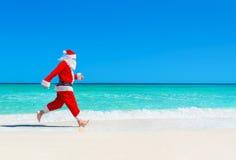 A corrida de Santa Claus do Natal na praia tropical contra ondas espirra Imagens de Stock Royalty Free