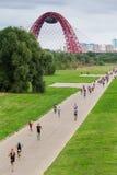 Corrida de Triathletes durante a competição do triathlon em Moscou com a ponte vermelha cabo-ficada de Jivopisny atrás Imagem de Stock Royalty Free