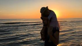 Corrida do pai e da filha ao longo da praia no por do sol video estoque