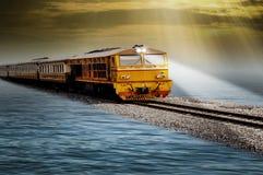 Corrida do trem no flutuador acima da água, nivelando o céu atrás dos arredores bonitos imagem de stock